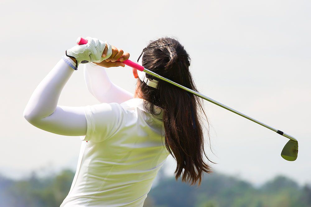 Female golfer swinging golf club